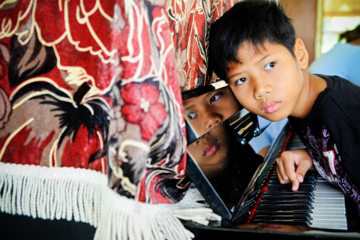 Bukit Harapan child with piano